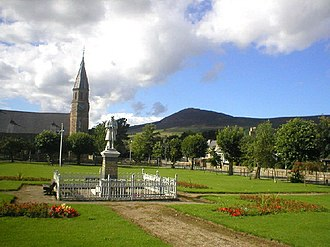 Rhynie, Aberdeenshire - The village green and war memorial, Rhynie Kirk behind the green, with Tap o' Noth in the distance