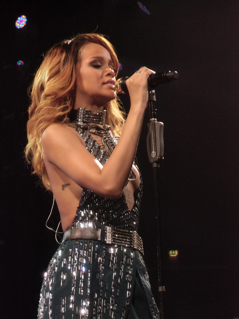 A dark blonde woman wearing a grayish shining outfit is performing