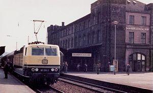 Saarbrücken Hauptbahnhof - Former 'island building' at Saarbrücken Hauptbahnhof with twin-system electric locomotive 181 216 on 10 September 1975