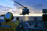 Sailor signals an SH-60R Sea Hawk helicopter aboard USS Donald Cook. (31978533344).jpg