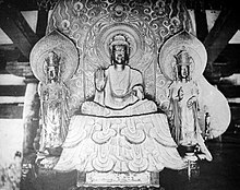 Front view of a central figure sitting cross-legged on a raised platform which is flanked by two smaller standing statues. The central figure has the palm of his right hand turned to the front. The attendants look identical, pointing upwards with their right hand and their left hand lifted halfway, touching the thumb with the middle finger. Each of the three statues has a halo.