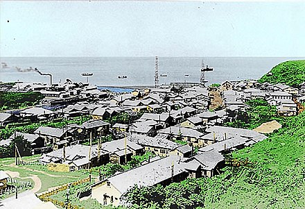 Shana Village in Etorofu (Showa period). There's a village hospital in the front, a factory in the left back with a fishery and a central radio tower (before 1945). Shana Village in Etorofu Island.JPG