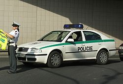 Older-model police car, white with green horizontal stripe