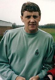 A brown-haired man in a light green sweatshirt with a neutral expression