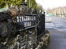 "A 19th- or early 20th-century black tile street sign with the words ""Stranmillis Road""."