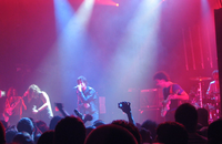 Two guitarists, a drummer, a bassist, and a vocalist are performing a song live on a stage lit by red and blue lights. The crowd, some of whom have their hands in the air, are visible in the foreground.