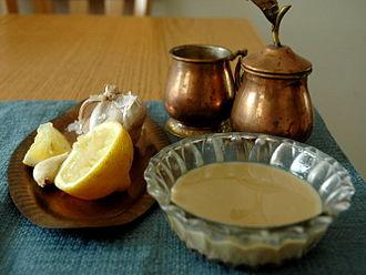 Tahini - Tahini next to lemon and whole garlic