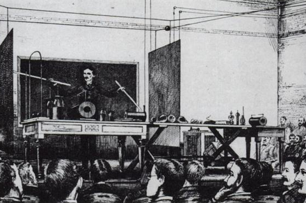"Tesla demonstrating wireless lighting by ""electrostatic induction"" during an 1891 lecture at Columbia College via two long Geissler tubes (similar to neon tubes) in his hands. TeslaWirelessPower1891.png"