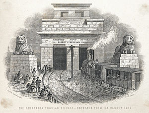 Britannia Bridge - A view of the entrance to the Britannia Bridge from the Bangor side, showing a steam train entering the bridge, people watching, two large stone lions and an inscription relating to the engineer, Robert Stephenson