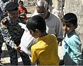 The commander of the 4th Iraqi Federal Police Division hands a bag of supplies to a young boy during a humanitarian aid distribution mission in Baghdad, Iraq, March 28, 2011 110328-A-QE777-037.jpg