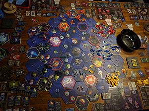 Twilight Imperium - An early-to-mid game board state. Games frequently have a large number of card decks, plastic pieces and cardboard tokens.