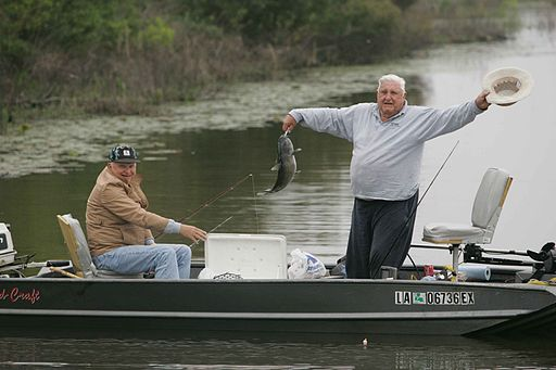 Two older men enjoying fishing from boat one man is standing and raising hat while showing the fish he just caught
