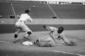 A baseball player slides into third base as an opposing player attempts to tag him