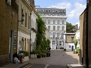 "Street - Typical service street (""mews"") in the Royal Borough of Kensington and Chelsea in London. Mews are typically found at the back of older housing terraces (rows of townhouses) in the UK, with a more elegant street in front of the terrace."