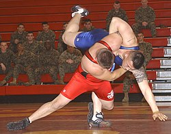 Two men wrestling in a gymnasium, watched by a group of uninformed soldiers