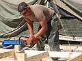 US Navy 030318-N-1050K-002 Steelworker 3rd Class Mike Freeman from Northern Hills, Calif., trims the excess off of the flooring frame during tent strong-backing efforts.jpg