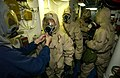 US Navy 030920-N-5471P-004 Damage Controlman 3rd Class Michael Muskett helps Ship's Serviceman 3rd Class Daniel Olaya don chemical protective gear.jpg