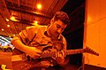 US Navy 040304-N-5945J-003 During a break from his duties at sea, Personnelman Seaman Apprentice David Smith plays his guitar in the ship's hangar bay aboard the aircraft carrier USS Harry S. Truman (CVN 75).jpg
