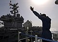 US Navy 050405-N-3241H-089 A Signalman uses semaphore to communicate via hand signals with Sailors aboard the Nimitz-class aircraft carrier USS Carl Vinson (CVN 70).jpg