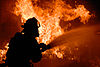 US Navy 070829-N-4965F-015 Flames push water from a fire hose back as a federal firefighter assigned to Navy Region Hawaii Federal Fire Department combats a fire during an aircraft firefighting training evolution with the Mobile.jpg