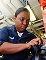 US Navy 081027-N-2456S-095 Damage Controlman 3rd Class Tosha Cowans places an adapter on the voice amplifier of the damage control facemask.jpg