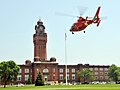 US Navy 090622-N-8848T-188 An HH-65C Dolphin helicopter from U.S. Coast Guard Air Station Traverse City, Mich., takes off from historic Ross Field in front of headquarters Building 1 at Naval Station Great Lakes.jpg
