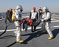 US Navy 110713-N-IO627-003 Sailors in fire protection suits move a mannequin to safety during a flight deck fire drill aboard the guided-missile de.jpg