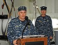 US Navy 120212-N-DX615-043 Capt. Humberto L. Quintanilla II reads his orders, as Capt. Donald R. Cuddington stands by to assume command of Amphibio.jpg