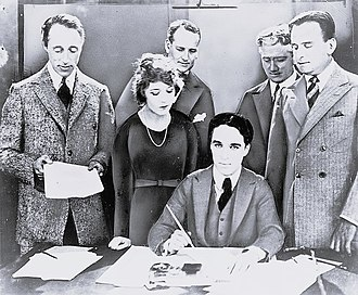 United Artists - Griffith, Pickford, Chaplin (seated), and Fairbanks at the signing of the contract establishing the United Artists motion-picture studio in 1919. Lawyers Albert Banzhaf (left) and Dennis F. O'Brien (right) stand in the background.