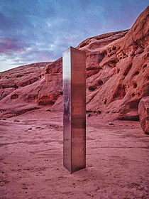 A metallic pillar with rectangular sides in a sandstone canyon