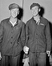 Two men in dark overalls and caps