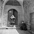 Vrouw en een zittende persoon, vermoedelijk bedelend, bij de toegangsdeur van de, Bestanddeelnr 255-0446.jpg