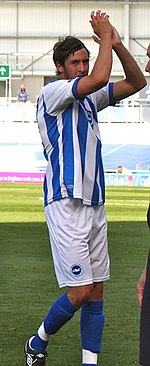 A young man, wearing a blue and white striped shirt, white shorts and blue socks, standing on a grass field. His arms are aloft, applauding towards the camera.