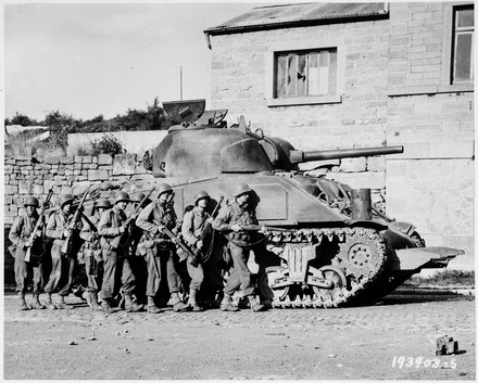 The 1943 improvement program added patches of applique armor to the sides of the turret and hull. This Sherman also sports a Culin hedgerow cutter, a 1944 field improvisation for breaking through the thick hedgerows of the Normandy bocage Yanks of 60th Infantry Regiment advance into a Belgian town under the protection of a heavy tank. - NARA - 531213.tif