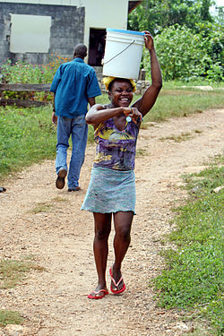 Young woman carrying a water bucket on her head, Clarendon, Jamaica.jpg