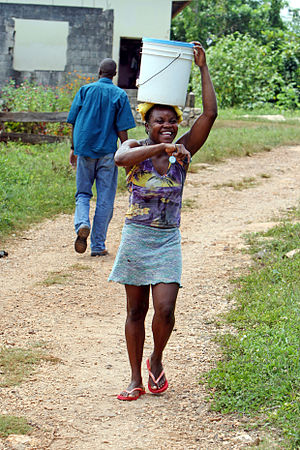 Clarendon Parish, Jamaica - Young woman carrying a water bucket on her head, Clarendon, Jamaica