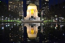 Photograph of a large memorial building at night. The building is being reflected in a body of water in front of it.
