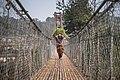 घाँसको भारि बोकेर झुलुङ्गे पुल तर्दै एक बृद्ध महिला.jpg