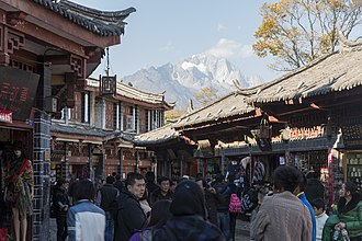 Old Town of Lijiang - Shops along the street with Jade Dragon Snow Mountain in the background