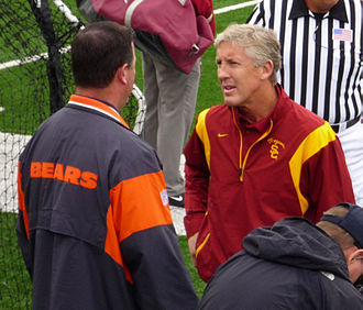 Pete Carroll - Pete Carroll talking to a pro scout before a game; during his tenure, 53 USC players were drafted by the NFL.
