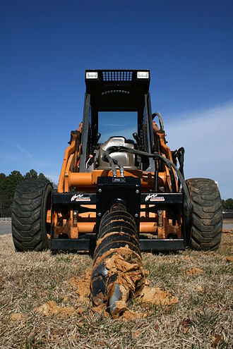 Auger (drill) - A skid-steer loader with an earth auger attachment.