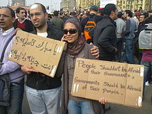 "A young man and a woman carrying the tops of cardboard boxes in a crowded group of people. On one boxtop is written ""People shouldn't be afraid of their governments. Governments should be afraid of their people"" in English and on the other, two questions in Arabic. He has a bandage on his forehead and she is wearing a headscarf and sunglasses."