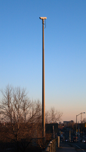 A video camera mounted on a tall pole on the side of a roadway. The camera is not pointing at the roadway visible at the bottom-right of the picture, but to the left.