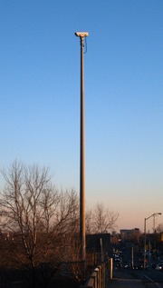 A video camera mounted on a tall cement pole on the side of a roadway. The camera is not pointing at the roadway visible at the bottom-right of the picture, but to the left.