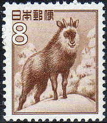 "A postage stamp featuring a sepia illustration of a goat-antelope standing on a snow-covered, forested hilltop. Stylized Japanese writing in the top left corner reads: ""日本郵便"". Immediately below this writing is a large ""8""."