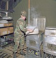 A mess management specialist lifts a steaming pot from a stove in a field kitchen set up by the 513th Military Intelligence Group - DPLA - 986778199ee01301a2a5de9c33b9faa9.jpeg