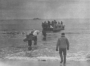 "USS Mobjack (AGP-7) - A landing party from Pioneer disembarks from a Landing Craft, Vehicle, Personnel (LCVP) (or ""Higgins boat"") on a beach in the Aleutian Islands, ca. 1949-1950. Pioneer is visible in the distance."