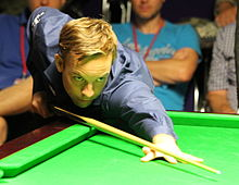 Ali Carter leaning over a table while lining up a shot