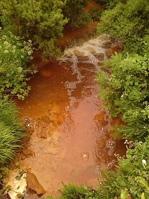 Environmental degradation - A stream in the town of Amlwch, Anglesey which is contaminated by acid mine drainage from the former copper mine at nearby Parys Mountain.