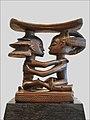 sculpture monoxyle avec une partie supérieure formant un croissant arrondi porté par deux personnages assis se faisant face